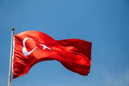 Turkish national flag with white star and moon in sky