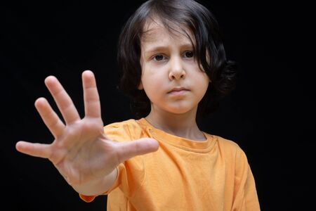 Boy showing stop gesture with his hand as prohibition  concept