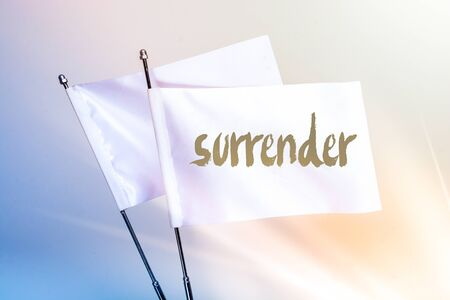 SURRENDER word written on white flag in display