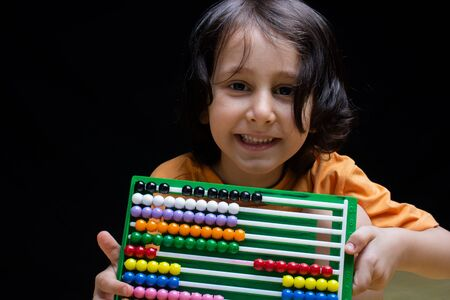 Portrait of a cute happy smiling boy with abacus in hand Stockfoto