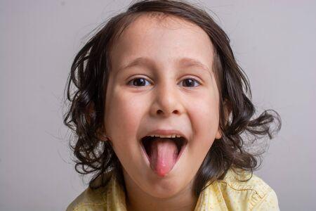 Closeup portrait of alittle boy sticking his tongue out 免版税图像