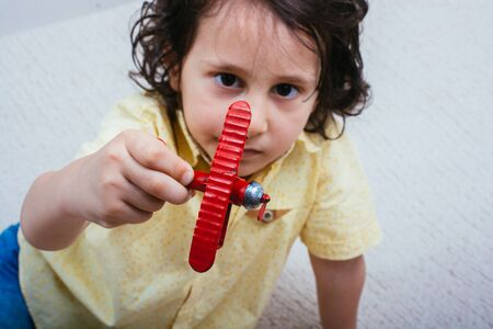 Red metal retro model airplane in the hand of a boy
