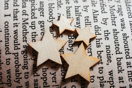Little wooden stars placed on book page Stok Fotoğraf
