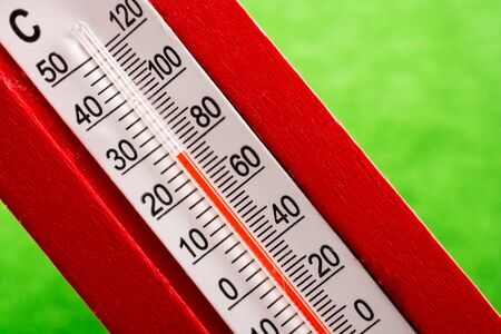 A red plastic thermometer on a green