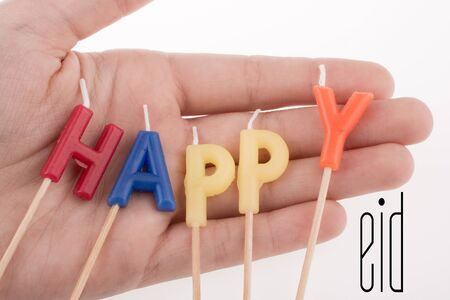 Color candles on sticks write the word happy