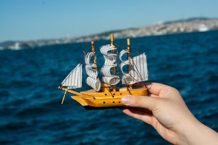 Child hand holding a boat model, sea in the
