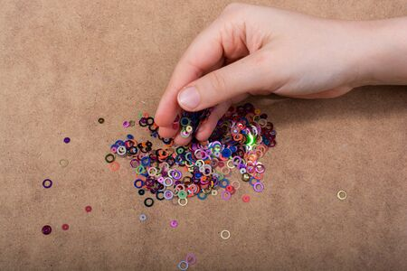 Hand holding decorative shiny colorful confetti on a wooden