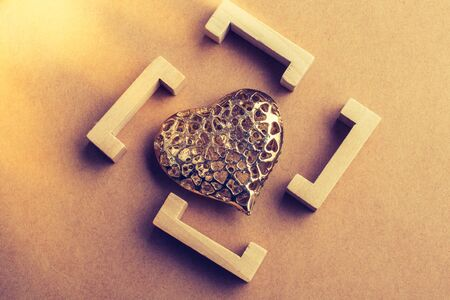 Gold color heart shaped  decorative object in brackets in view Stock Photo