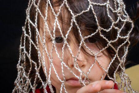 Little boy  trapped in a net as captivity