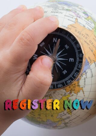 Hand holding compass on globe with register now wording on it