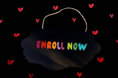 Hand holding sign board  with  Enroll now wording on it