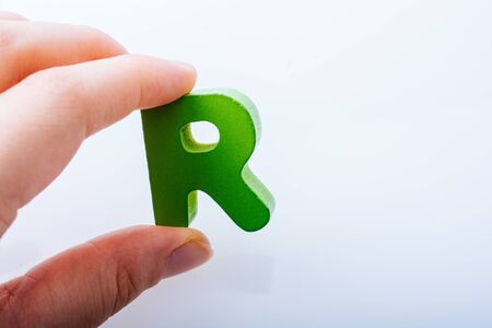 Hand holding letter cube R of made of wood Stock fotó