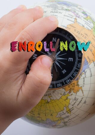 Hand holdingcompass on globe with Enroll now wording on it 版權商用圖片