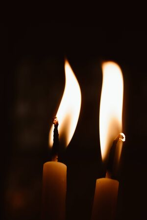Candles burning with yellow flames in the dark