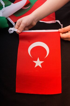 Child hand holding Turkish flag with white star and moon Stok Fotoğraf - 132025946