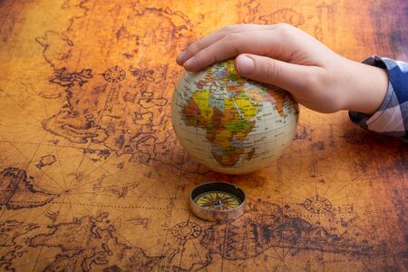 Compass on map beside a globe under hand