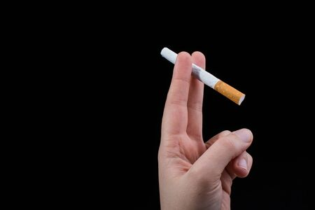 Hand is holding a cigarette on black background Stock Photo