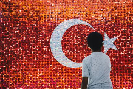 Boy standing before Turkish national flag with white star and moon