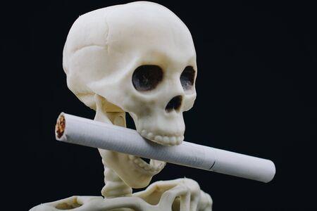"""Menschliches Skelett mit Zigarette. """"Weltnichtrauchertag"""" mit dem Rauchen aufhören oder aufhören!"""