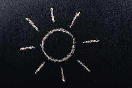 Hand drew sun by chalk with light ray shape on blackboard background Standard-Bild - 134792321