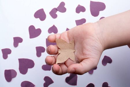 Paper butterfly and red paper hearts in hand Stock Photo