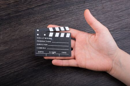 Hand holding movie  clapper on a dark background Stock fotó