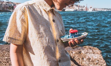 Child holding a boat model cheerfully, sea in thebackground.