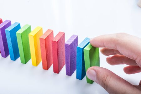 Colorful Domino Blocks in hand on a white background