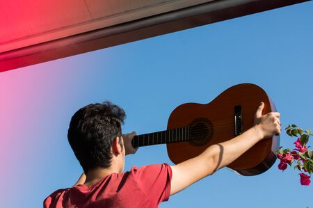 Young man rising an accoustic guitar in the blue sky Фото со стока