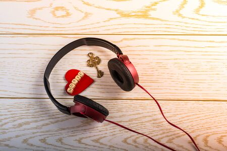 Red headphones, key and music written red heart  on a wooden background