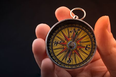 Hand is holding a magnetic compass on black background