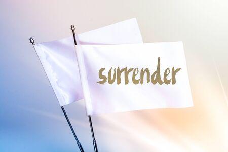 SURRENDER word written on white flag in display