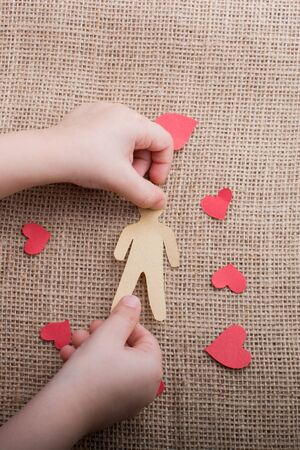 Man and heart shape cut out of paper in hand