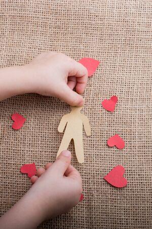 Uomo e forma di cuore ritagliati di carta in mano