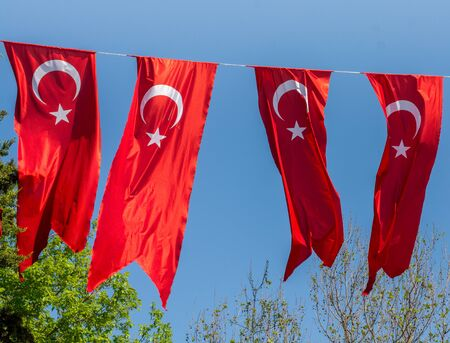 Turkish national flags hang in view in open air