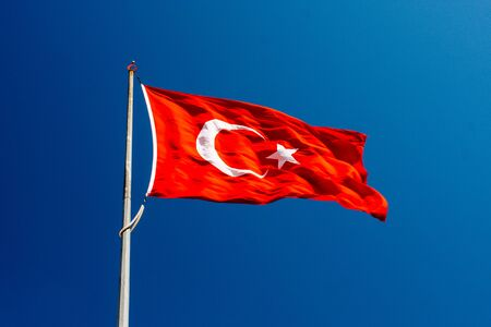 Turkish national flag with white star and moon on a pole in sky
