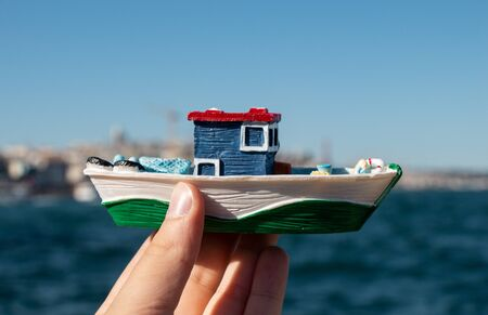 Child hand holding a boat model, sea in the background. Banco de Imagens