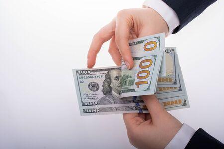 Businessman holding US dollar banknote money on white background