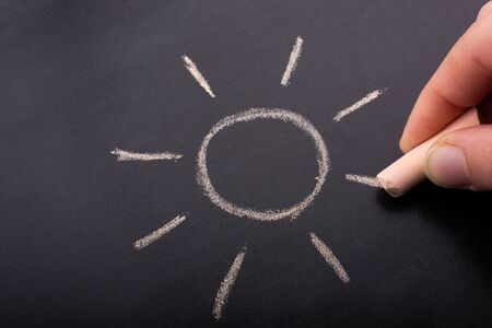 Hand drawing sun by chalk with light ray shape on blackboard background