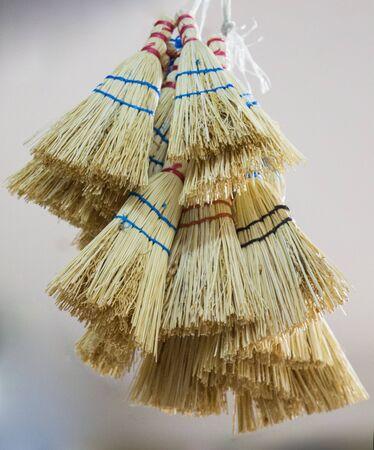 Set of yellow straw broom in a bazaar