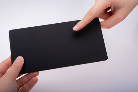 Rectangular shaped black notice board in hand on white background