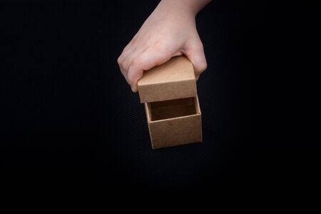 Hand opening a brown cardboard box on black backgrounds
