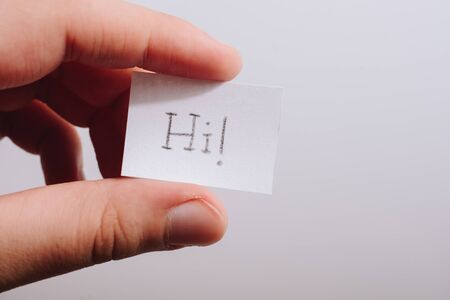 Hand holding notepaper with HI wording on white background