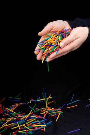 Hand letting coloured wooden  sticks fall on black background