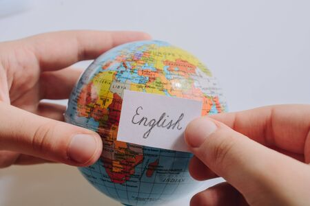 Hand holding notepaper with English wording on model globe Banco de Imagens