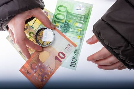 Compass in hand on Euro banknotes with Euro currency finance direction