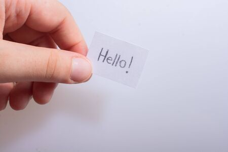 Hand holding notepaper with HELLO wording on white background Banco de Imagens