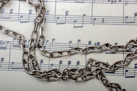 Metal chain placed on a paper with musical notes