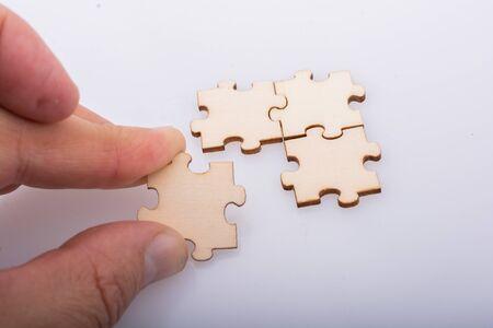Hand holding piece of jigsaw puzzle as problem solution concept Banco de Imagens