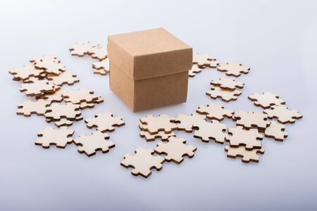 Pieces of jigsaw puzzle around box as problem solution business concept